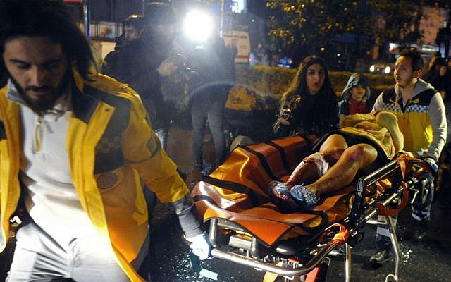 Medics carry a wounded person at the scene of a shooting attack at a popular nightclub in Istanbul, early Sunday, Jan. 1, 2017. (IHA via AP)