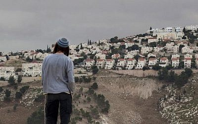 In this Wednesday, Dec. 5, 2012 file photo, a Jewish settler looks at the West Bank settlement of Ma'ale Adumim, from the E-1 area on the eastern outskirts of Jerusalem. (AP Photo/Sebastian Schooner)