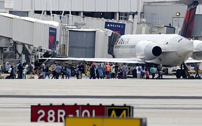 People stand on the tarmac at the Fort Lauderdale-Hollywood International Airport after a shooter opened fire inside the terminal, killing several people and wounding others before being taken into custody, Friday, Jan. 6, 2017, in Fort Lauderdale, Fla. (AP Photo/Lynne Sladky)