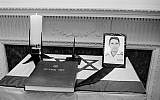 A photo of Israeli Col. Yosef Alon and a visitors book sit on a flag-draped memorial table at the Israeli embassy in Washington, July 1, 1973.  (AP Photo/stf)