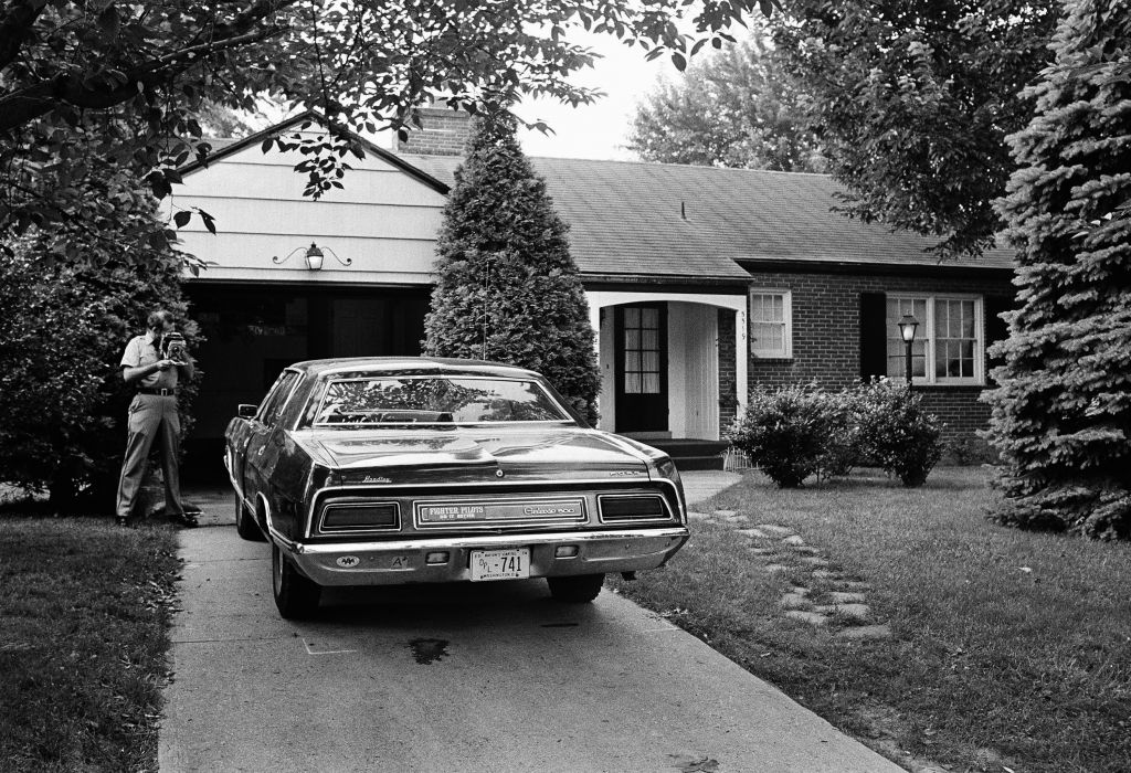 A police officer photographs the car from which Col. Yosef Alon, air attache to the Israeli Embassy in Washington, was stepping when he was shot to death July 1, 1973 outside his Bethesda, MD., home. (AP Photo/John Duricka)