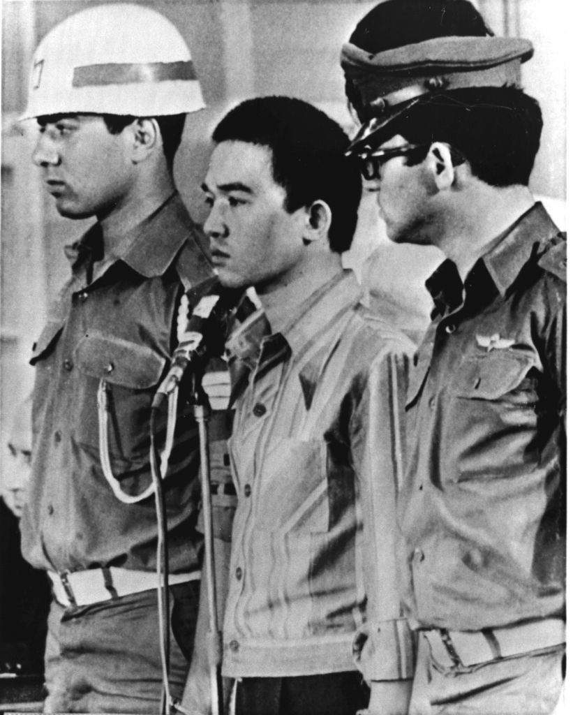 In this Monday, July 17, 1972 file photo, Japanese terrorist Kozo Okamoto, center, surrounded by guards, listen in a Lod, Israel, courtroom, as a guilty verdict is delivered for his part in the May 30 massacre of 28 people in the Lod airport. (AP Photo, File)