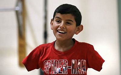 In this Dec. 10, 2016 photo, Syrian refugee Ahmad Alkhalaf smiles while playing with friends during a day camp for local Muslim children in Sharon, Mass. (AP Photo/Charles Krupa)