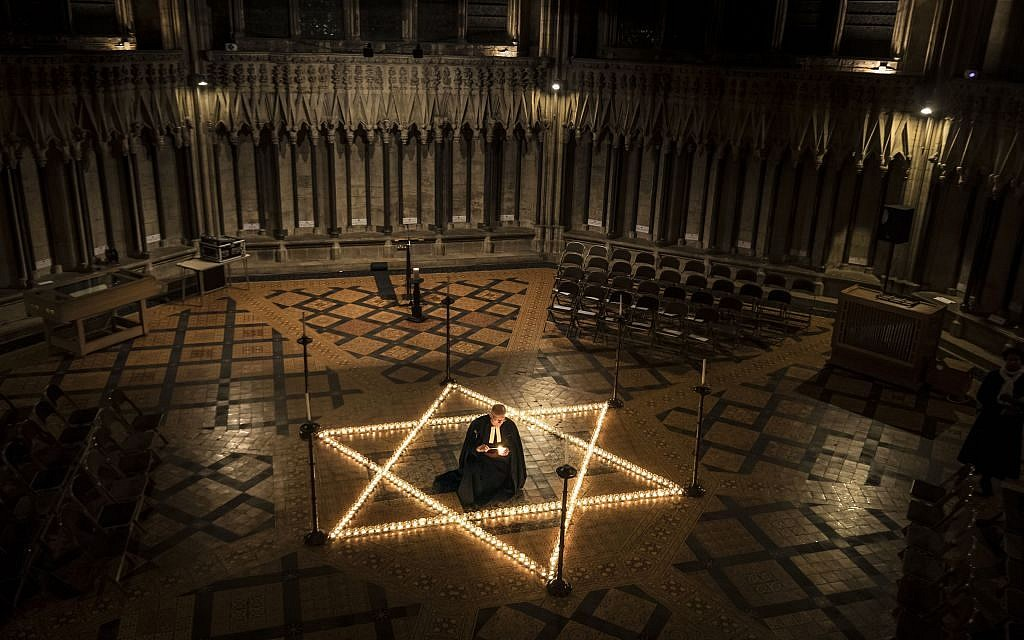 Canon Chancellor Christopher Collingwood helps light one of 600 candles in the shape of the Star of David to commemorate Holocaust Memorial Day at York Minster, York,, England, Thursday, Jan. 26, 2017. (Danny Lawson/PA via AP)
