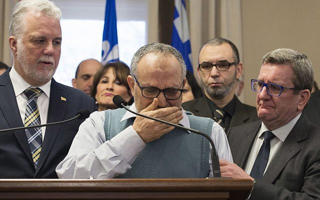 Mohamed Labidi, the vice-president of the mosque where an attack happened, is comforted by Quebec Premier Philippe Couillard, left, and Quebec City mayor Regis Labeaume, right, during a news conference Monday, Jan. 30, 2017, about the fatal shooting at the Quebec Islamic Cultural Centre on Sunday. (Jacques Boissinot/The Canadian Press via AP)
