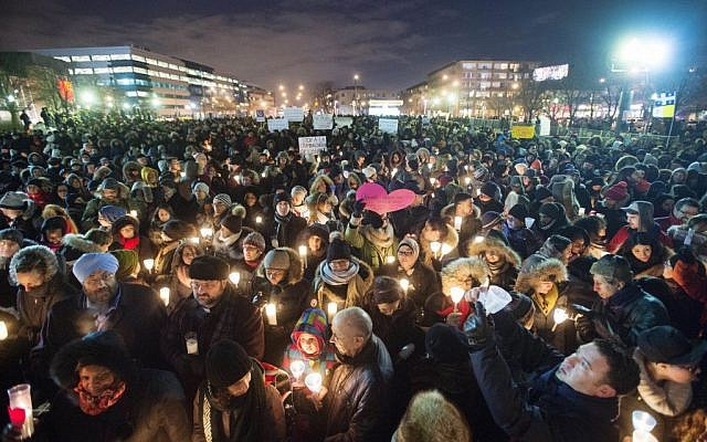 People hold candles for victims of Sunday's deadly shooting at a Quebec City mosque, during a vigil in Montreal on Monday, Jan. 30, 2017. (Ryan Remiorz/The Canadian Press via AP)