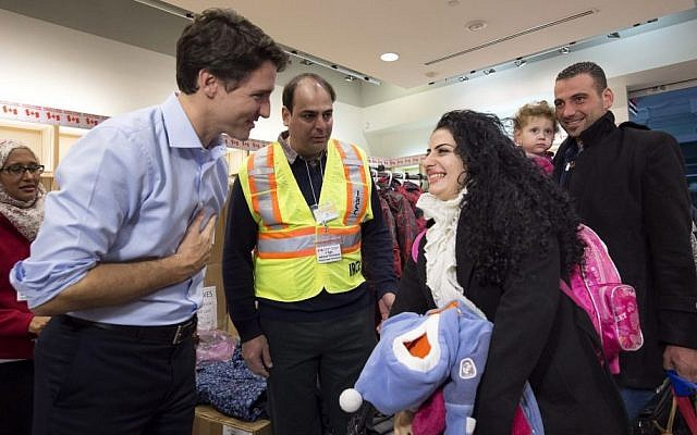 Canadian Prime Minister Justin Trudeau, left, greets Georgina Zires, center, Madeleine Jamkossian, second right, and her father Kevork Jamkossian, refugees fleeing from Syria, as they arrive at Pearson International airport, in Toronto, December 11, 2015. (Nathan Denette/The Canadian Press via AP)