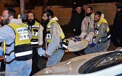 ZAKA rescue personnel carry the bodies of family members at the scene where a woman and four children were killed in a fire in what police suspect was a murder-suicide at an apartment in Jerusalem, January 1, 2017.  (Moshe Mizrahi/ZAKA)