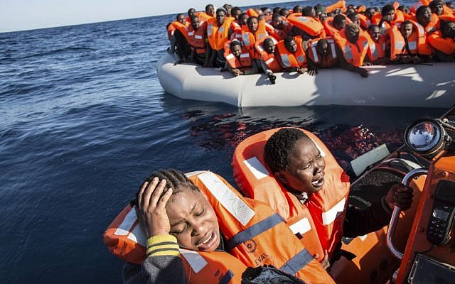 A migrant reacts on being rescued by the MV Aquarius, after 191 people and two corpses were recovered Friday Jan. 13, 2017, from international waters in the Mediterranean Sea about 22 miles north of Sabrata, Libya. (AP Photo/Sima Diab)