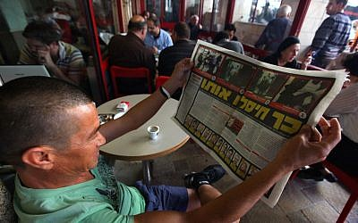 """A man reading a copy of Yedioth Ahronoth in Jerusalem on Febuary 16, 2010. The headline reads: 'This is how they assassinated him."""" (Kobi Gideon / FLASH90)"""