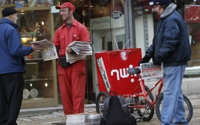 A man passes out the free newspaper Israel Hayom to passersby on Ben Yehuda in Jerusalem. January 4, 2011. (Miriam Alster/FLASH90)