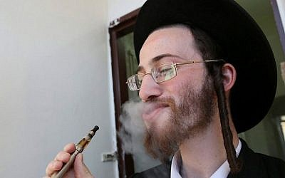 An ultra-Orthodox Jewish man seen smoking an electric cigarette. September 23, 2012. (Nati Shohat/Flash90)