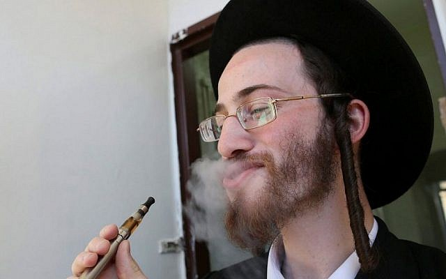 An ultra-Orthodox Jewish man seen smoking an electric cigarette, September 23, 2012. (Nati Shohat/Flash90)