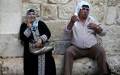 An Arab man and woman seen smoking cigarettes as they sit near the steps outside of the Church of the Holy Sepulchre in Jerusalem's Old City. November 18, 2013. (Nati Shohat/Flash90)