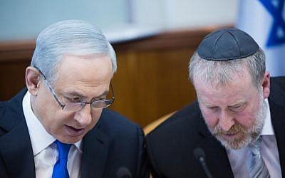 Prime Minister Benjamin Netanyahu, left, speaks with then-cabinet secretary Avichai Mandelblit, right, during a weekly cabinet meeting in Jerusalem on December 20, 2015. (Yonatan Sindel/Flash90)