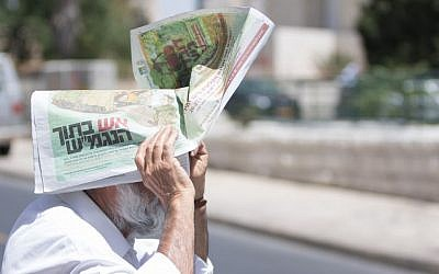 A man carries a newspaper over his head to protect himself from the sun, on a warm summer day in Jerusalem. May 22, 2016. (Zack Wajsgras/FLASH90)
