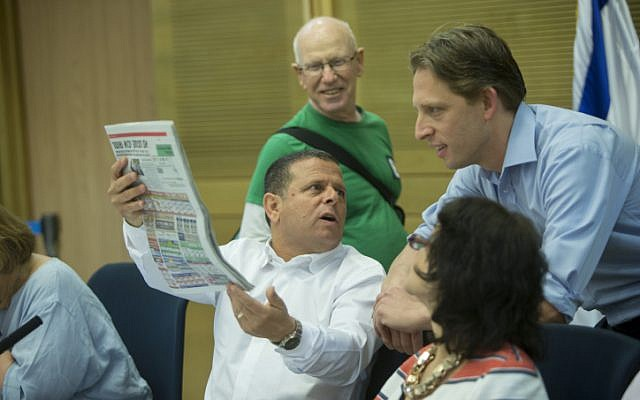 Zionist Union MK Eitan Cabel (D-C) holds up the Israel Hayom daily newspaper during an Economy Committee meeting regarding the new public broadcasting corporation at the Knesset on August 2, 2016. (Yonatan Sindel/Flash90)