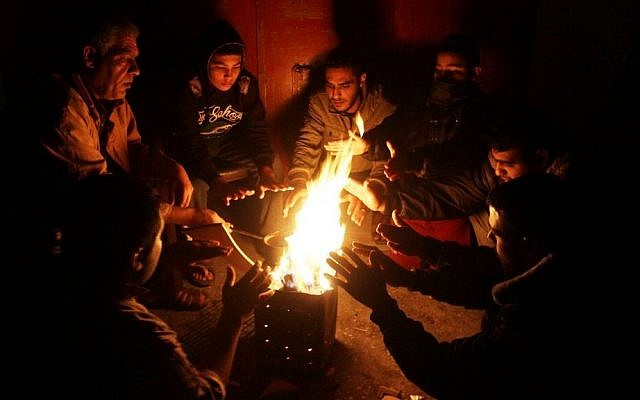 Palestinians warm themselves around a fire during a winter storm, in Rafah, Gaza Strip, on December 1, 2016. (Abed Rahim Khatib/Flash90)