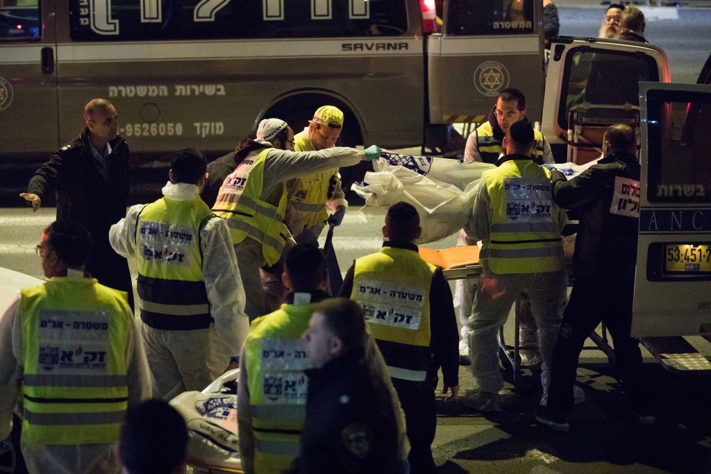 Zaka rescue personnel carry the bodies of family members at the scene where a woman and four children were killed in a fire at an apartment in Jerusalem on Sunday, January 1, 2017, in what may have been caused by a severe case of post-partum depression (Yonatan Sindel/Flash 90)
