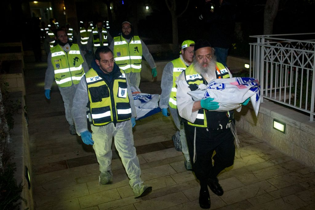 ZAKA rescue personnel carry the bodies of family members at the scene where a woman and four children were killed in a fire in what police suspect was a murder-suicide at an apartment in Jerusalem, January 1, 2017. (Yonatan Sindel/Flash90)