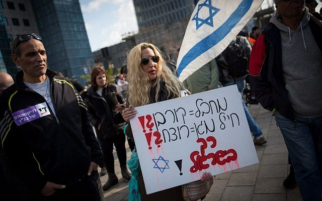 """A supporters of Elor Azaria holding a sign reading """"terrorist = victim?! protecting soldier = killer?! only in Israel!"""" outside the Kirya military court, where Azaria was convicted of manslaughter on January 4, 2017. (Miriam Alster/FLASH90)"""