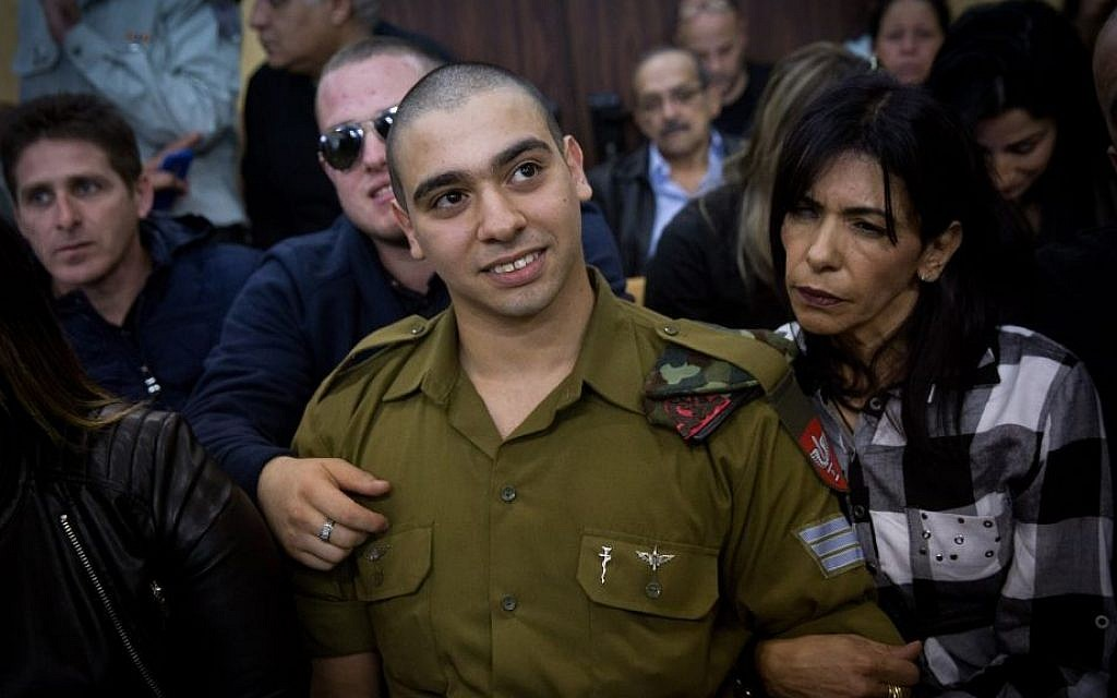 IDF Sgt. Elor Azaria, the Israeli soldier who shot a Palestinian attacker, in Hebron, surrounded by family and supporters as he arrives to hear his verdict in a courtroom at the Kirya military base, Tel Aviv, January 4, 2017. (Miriam Alster/Flash90)