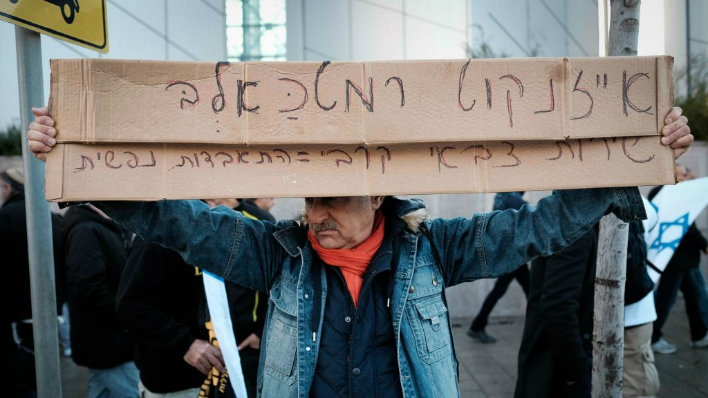 A protester against the verdict in the Azaria trial holds up a sign outside the Kirya military headquarters in Tel Aviv on January 4, 2017, that calls IDF Chief of Staff Lt. Gen. Gadi Eisenkot a 'dog' (Tomer Neuberg/Flash90)