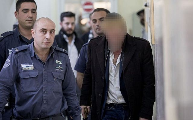 A 54-year-old man arrested for making threats against a judge in the military trial of IDF soldier Elor Azaria is escorted by prison guards into the Jerusalem Magistrate's Court on January 5, 2017. (Yonatan Sindel/Flash90)