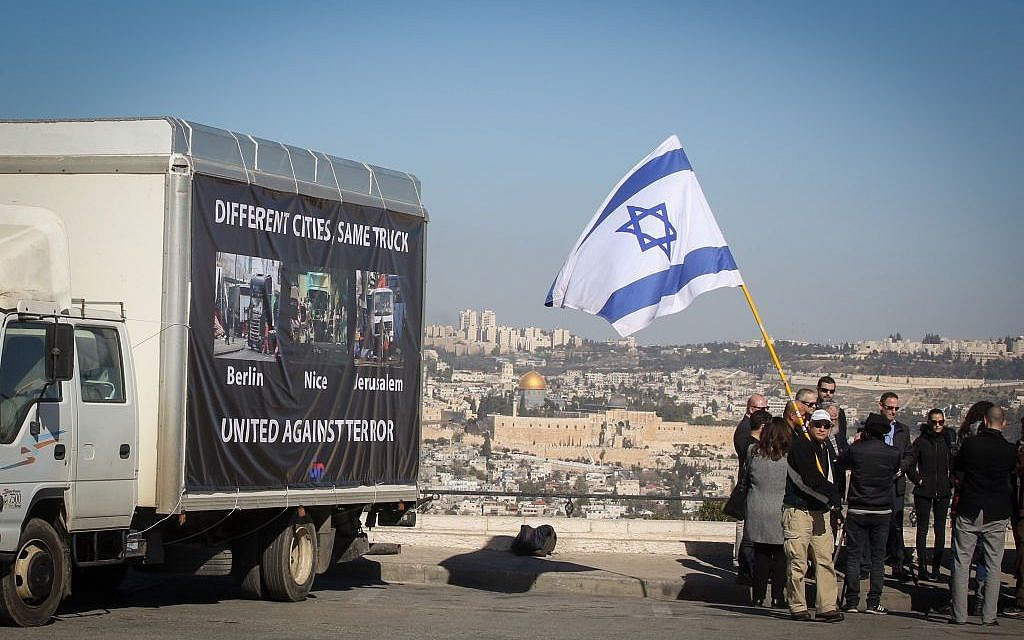 Participants in a support rally carry the Israeli flag as they walk past a truck showing images from terror attacks in Berlin, Nice and Jerusalem, all carried out using trucks as lethal weapons, near the site of the Jerusalem attack on January 11, 2017. (FLASH90)