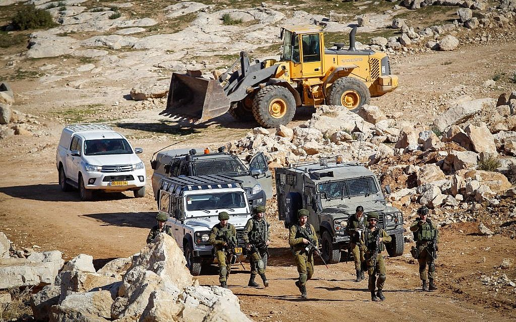 Soldiers guard as an army bulldozer blocks the road near the West Bank village of Bani Naim, January 11, 2017. (Wisam Hashlamoun/Flash90)