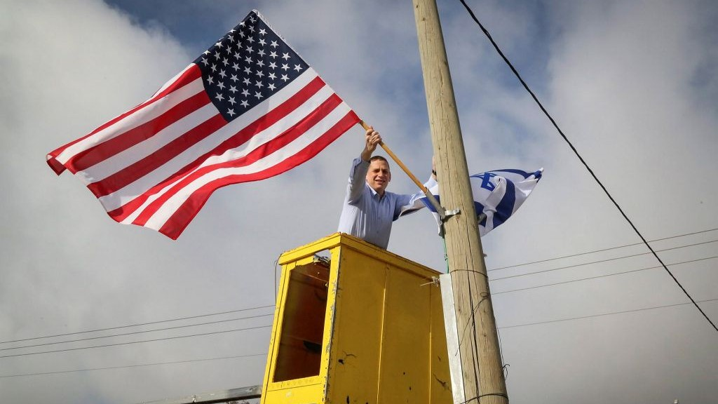Chairman of the Etzion Bloc regional council Moshe Saville hangs an American flag at the Gush Etzion Junction in the West Bank, ahead of the swearing-in ceremony of incoming US President Donald Trump, on January 19, 2017. (Gershon Elinson/Flash90)