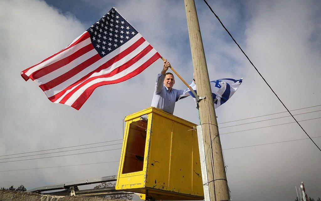 An official from Gush Etzion Regional Council hangs a US flag from a lamppost a day before the inauguration of Donald Trump as president, on January 19, 2017 (Photo by Gershon Elinson/Flash90)
