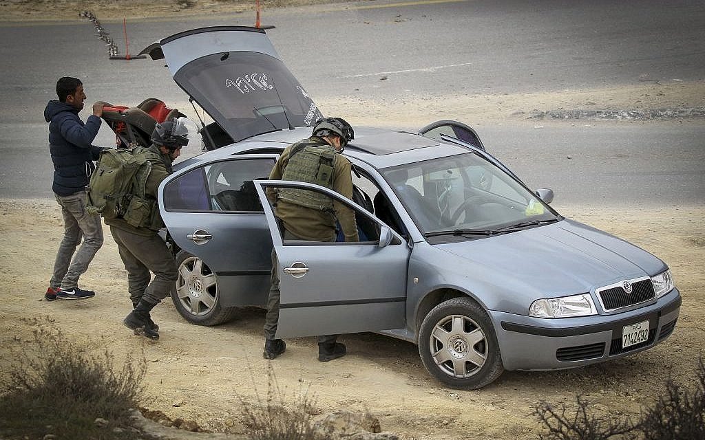 Border Police officers search a Palestinian vehicle in the West Bank village of Bani Na'im on January 26, 2017 (Photo by Wisam Hashlamoun/Flash90)
