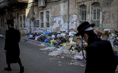 Ultra-Orthodox men walk past piles of garbage caused by a strike of the Jerusalem municipality, in Jerusalem's Mea Shearim neighbourhood, on January 30, 2017.(Yonatan Sindel/Flash90)