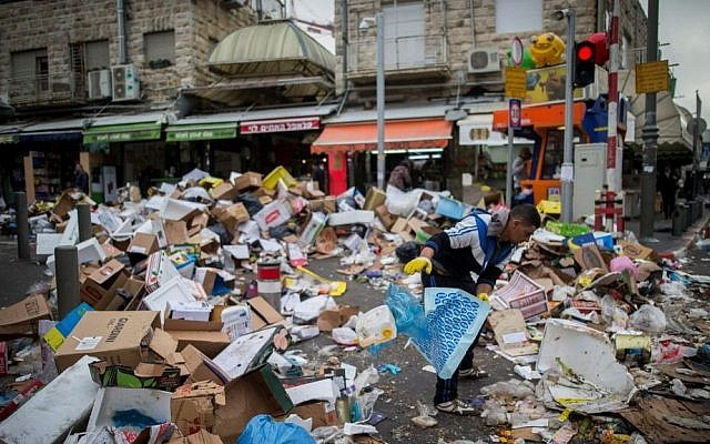 People walk past piles of garbage caused by a strike of the Jerusalem municipality, at the Mahane Yehuda Market in Jerusalem, on January 31, 2017. (Yonatan Sindel/Flash90)