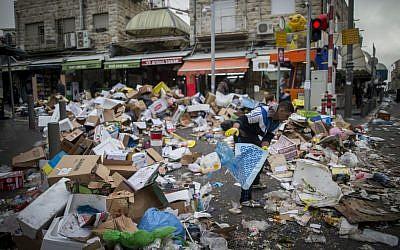People walk past piles of garbage at the Mahane Yehuda Market in Jerusalem, caused by a strike of the Jerusalem municipality, January 31, 2017. (Yonatan Sindel/Flash90)