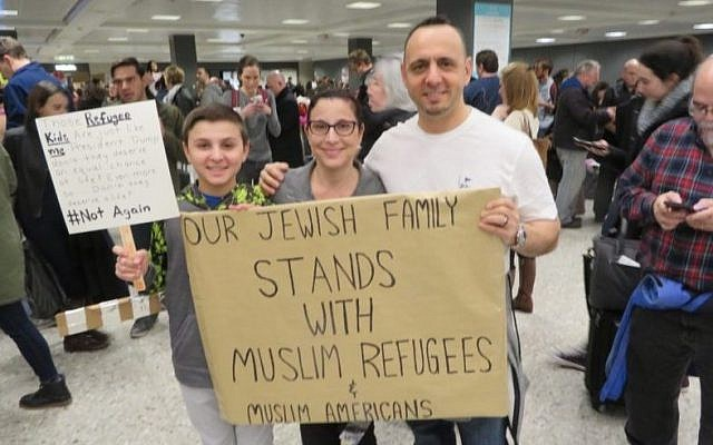 Jacob, left, Miri and Tal Zlotnitsky holding up a poster welcoming Muslim arrivals at Dulles International Airport in Virginia, Jan. 28 2017. (Ron Kampeas)