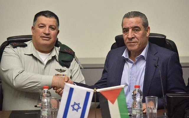 File: Then-coordinator of government activities in the territories (COGAT) Maj. Gen. Yoav Mordechai, left, and the Palestinian Authority's Civil Affairs Minister Hussein al-Sheikh sign an agreement to revitalize the Israeli-Palestinian Joint Water Committee, January 15, 2017. (Courtesy COGAT)