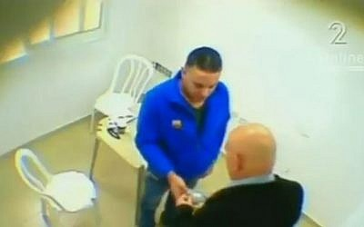 Footage appearing to show MK Basel Ghattas handing over a package to Palestinian prisoner Walid Daka (Screen capture: Channel 2)