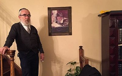 Israel Shemtov, one of Crown Heights' most distinguished tailors, poses next to a photograph of the Lubavitcher Rebbe, Menachem Mendel Schneerson. (Madison Margolin/Times of Israel)