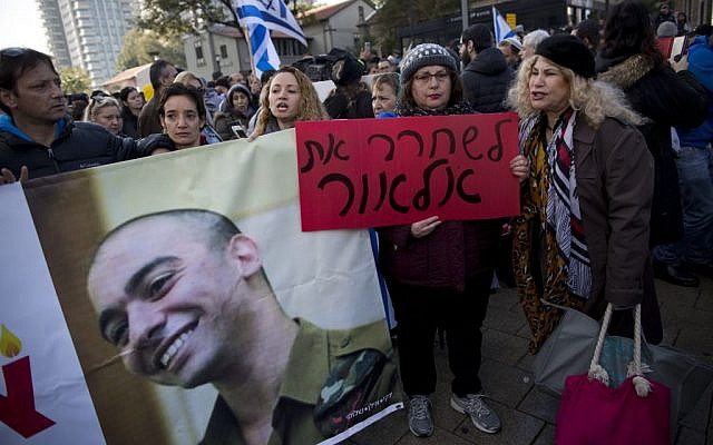 "Supporters of Sgt. Elor Azaria hold his photo and shout slogans outside the Israeli military court in Tel Aviv, Israel, Wednesday, January 4, 2017. The Hebrew sign reads ""Free Elor."" (AP/Oded Balilty)"