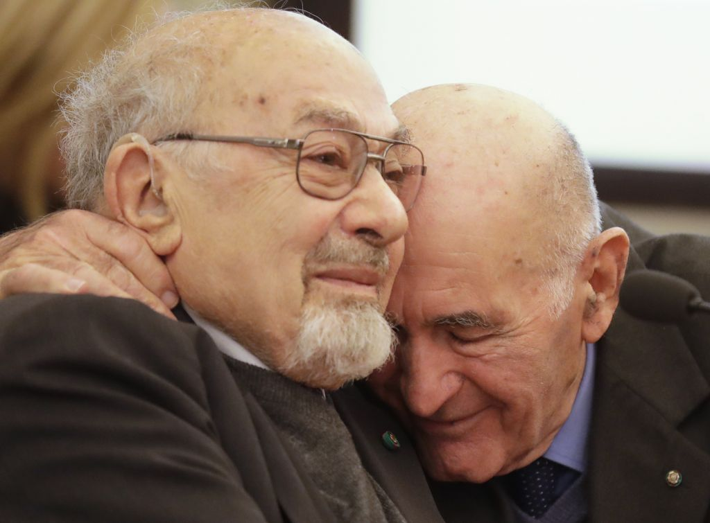 Holocaust survivors Sami Modiano, right, and Piero Terracina hug each other during an event on International Holocaust Remembrance Day, at Rome's Capitol Hill, Friday, Jan. 27, 2017. (AP Photo/Alessandra Tarantino)