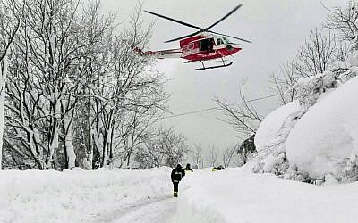 An Italian firefighters helicopter flies during rescue operations in the area where an hotel was hit by an avalanche in Farindola, Italy, early Thursday, Jan. 19, 2017 (Matteo Guidelli/ANSA via AP)