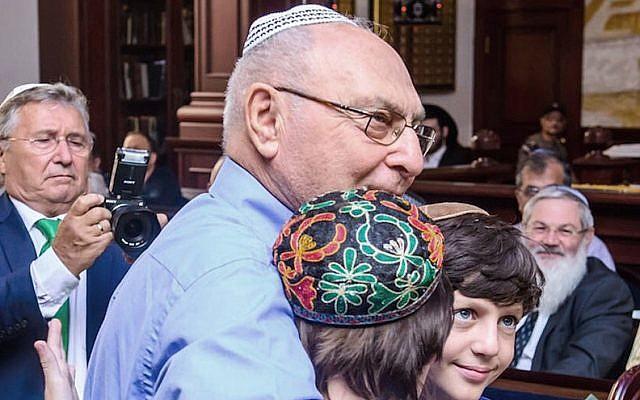 Haim Erez hugging the children of Yanush Ben Gal in Kazan, Sept. 4, 2016. (Limmud FSU via JTA)