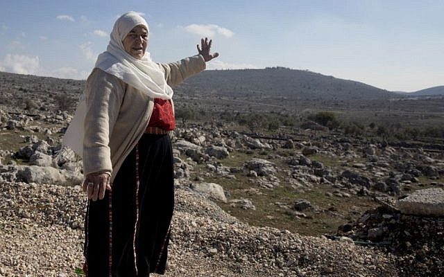 In this Monday, January 1, 2017 photo, Maryam Abdel-Kareem, an 82-year-old Palestinian, points to land held by the Jewish settlement of Amona, an unauthorized outpost in the West Bank, near the village of Silwad. (AP/Majdi Mohammed)