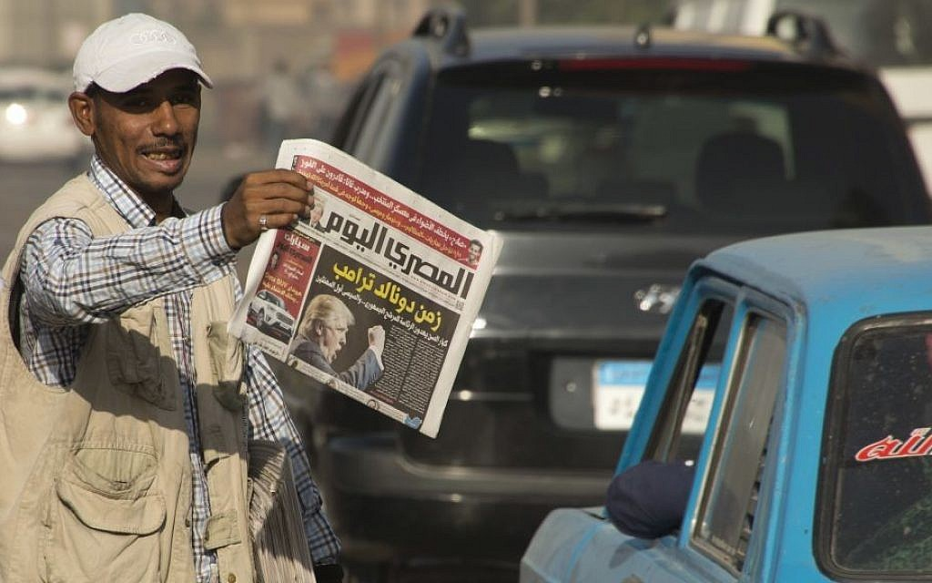 """An Egyptian newspaper vendor holds copies of local newspapers fronted with a picture of President-elect Donald Trump with Arabic headline that reads, """"Trump era"""", November 10, 2016. (AP Photo/Amr Nabil, File)"""