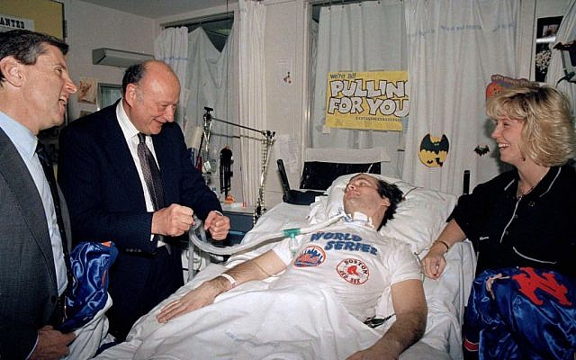 NYPD Officer Steven McDonald, paralyzed after being shot in Central Park earlier in the year, receives a New York Mets baseball jacket from Mets' president Fred Wilpon, left, in McDonald's room in New York's Bellevue Hospital, October 30, 1986. (AP/Mario Suriani)