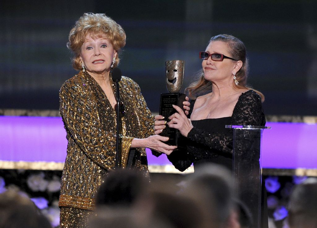 In this Jan. 25, 2015, file photo, Carrie Fisher, right, presents her mother Debbie Reynolds with the Screen Actors Guild life achievement award at the 21st annual Screen Actors Guild Awards at the Shrine Auditorium in Los Angeles. (Photo by Vince Bucci/Invision/AP, File)