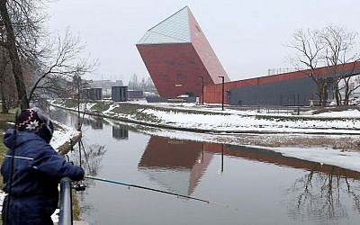 A woman fishes near the Museum of the Second World War, an ambitious new museum under creation for nine years which is almost completed, in Gdansk, Poland, on Monday, January 23, 2017. (AP Photo/Czarek Sokolowski)