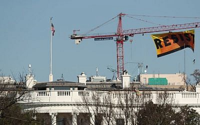 "Greenpeace protesters unfurl a banner that reads ""Resist"" at the construction site of the former Washington Post building, near the White House in Washington, Wednesday, Jan. 25, 2017, after police say protesters climbed a crane at the site refusing to allow workers to work in the area. (AP Photo/Andrew Harnik)"